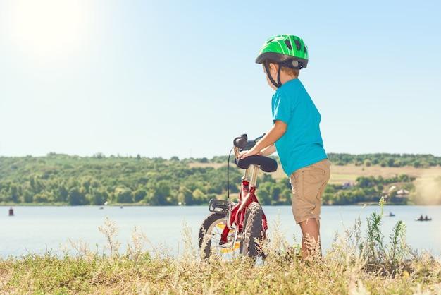 川の近くで自転車に乗る少年