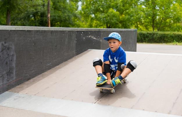 Мальчик катается на своем скейтборде, сидя на нем, пока он спускается по склону на пандусе в скейт-парке с выражением благоговейной сосредоточенности и удовольствия.
