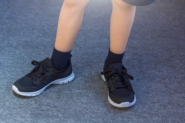 Ноги молодого мальчика в текстильных модных черных кроссовках