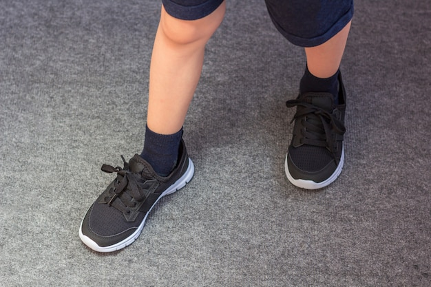 Young boy's legs in textile fashion black sneakers. children's trendy casual outfit and street fashion. top view, close up