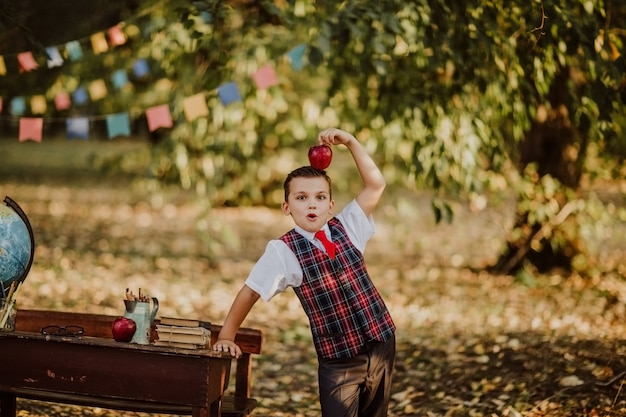 Young boy in school uniform posing with newton apple near an old wooden desk in the park