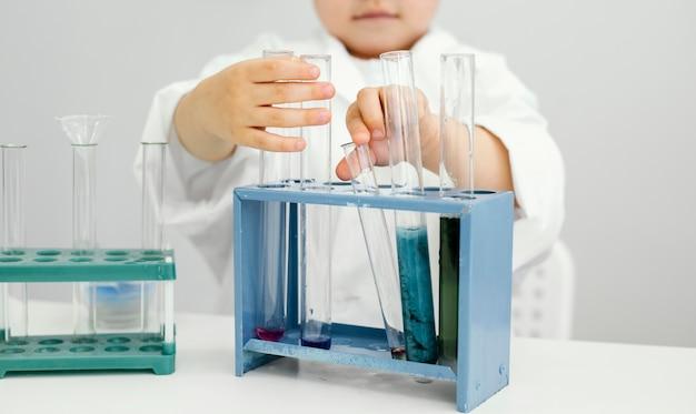 試験管を使って実験室で実験をしている少年科学者