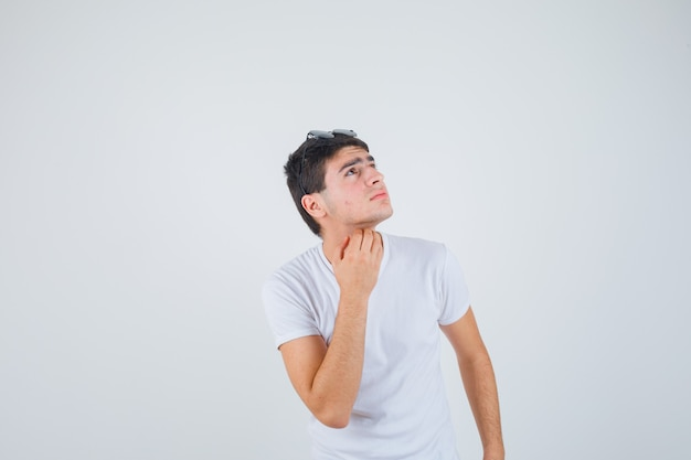 Young boy scratching throat while looking upward in t-shirt and looking pensive , front view.