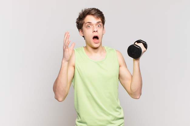 Young boy screaming with hands up in the air, feeling furious, frustrated, stressed and upset. dumbbell concept