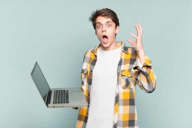 少年は空中で手を上げて叫び、激怒し、欲求不満を感じ、ストレスを感じ、動揺しました。ノートパソコンのコンセプト