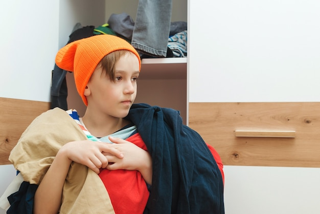 옷장에서 옷을 찾는 어린 소년. 집안일 집안일. 옷장과 탈의실이 엉망입니다.