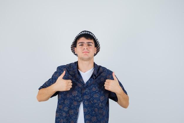 白いtシャツ、花柄のシャツ、キャップで二重の親指を示し、自信を持って見える少年。正面図。