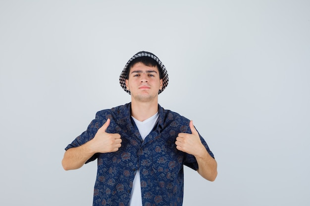 Young boy showing double thumbs up in white t-shirt, floral shirt, cap and looking confident. front view.