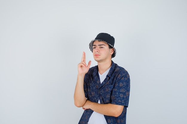 Young boy showing gun gesture, holding hand under elbow in white t-shirt, floral shirt, cap and looking confident , front view.