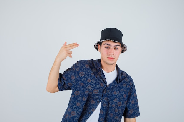 Young boy showing gun gesture near head in white t-shirt, floral shirt, cap and looking serious. front view.