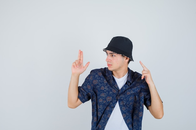 Young boy showing gun gesture, raising index finger in white t-shirt, floral shirt, cap and looking confident. front view.