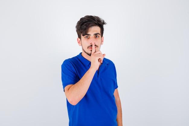 파란색 티셔츠에 침묵 제스처를 표시하고 심각한 찾고 어린 소년. 전면보기.