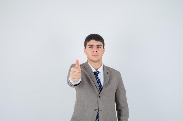 공식적인 양복에 엄지 손가락을 표시 하 고 자신감, 전면보기를 찾고 어린 소년.