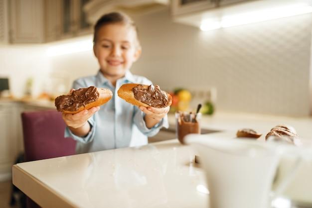 若い男の子は自然な溶かされたチョコレートのサンドイッチを示しています。
