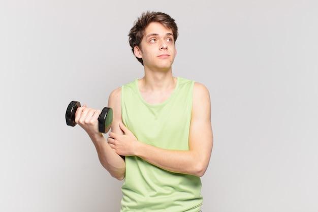 肩をすくめる少年は、混乱して不安を感じ、腕を組んで困惑した表情で疑っています。ダンベルのコンセプト