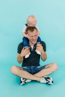Молодой мальчик сидит на его шее отцов изолированной на голубой предпосылке.