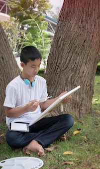 Young boy sitting on green grass ground floor,using brush  painting color on canvas with interested feeling,good hobby.