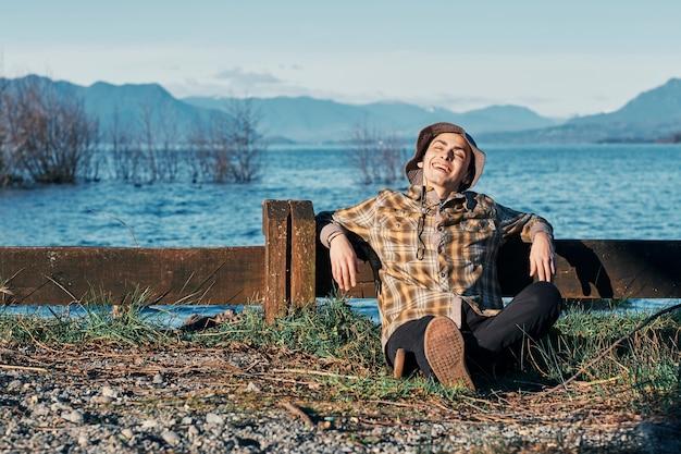 Молодой мальчик, сидя на лугу возле озера или моря, улыбается и наслаждается отпуском.