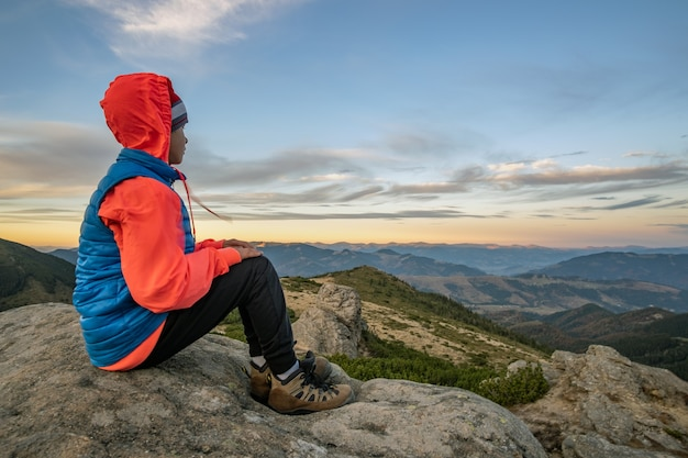 Young boy sitting in mountains enjoying view of amazing mountain landscape