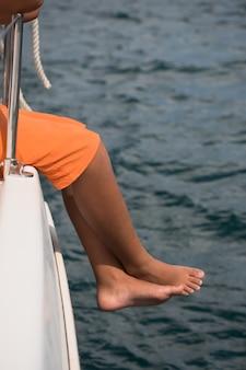 요트쪽에 앉아 어린 소년입니다. 바다를 건너는 여행