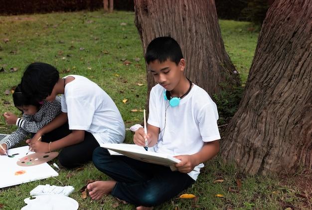 그의 sister.he 옆에 녹색 잔디 1 층에 앉아 어린 소년 행복 한 느낌으로 캔버스에 색상을 그림입니다.