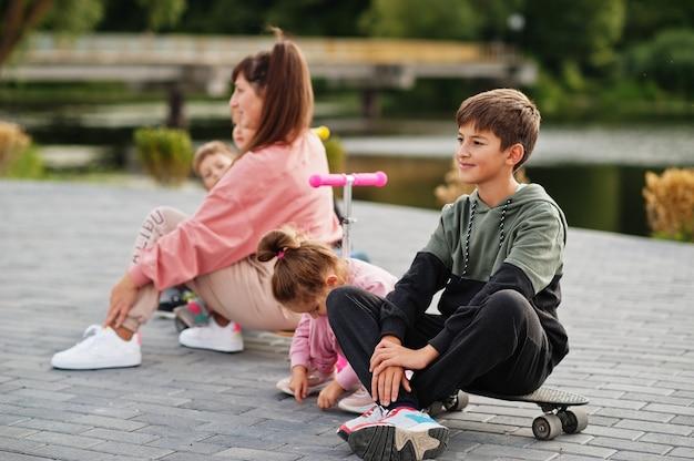 スケートに座っている少年。スポーツの家族は、スクーターやスケートで屋外で自由な時間を過ごします。