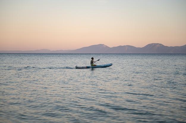 夕方の海を漕ぐスタンドアップパドルボードに座っている少年。夕日が彼の後ろに色付きの空を沈めています。