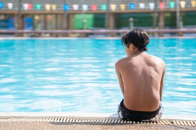 Young boy sitting at the side of the swimming pool looking sad