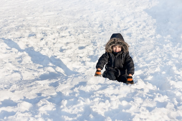 Young boy sitting on the snow