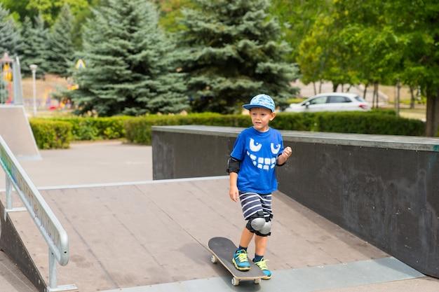 浅いスロープに立って誰かを待っているか何かを見ているスケートパークでスケートボードをしている少年