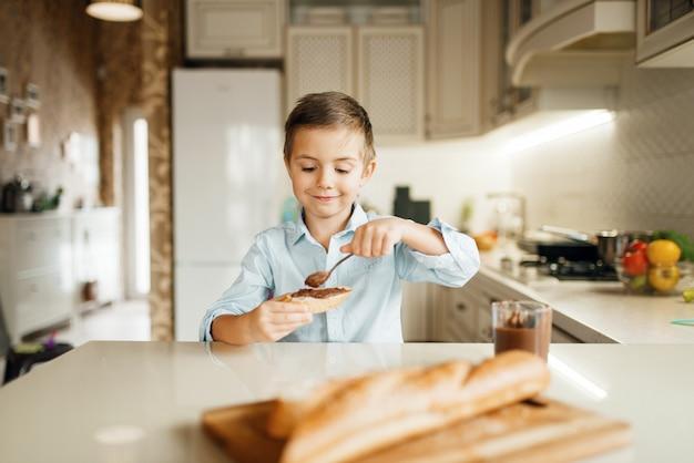 若い男の子はパンに溶かしたチョコレートを塗ります。