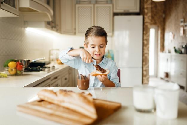 若い男の子はパンに溶かしたチョコレートを塗抹標本します。