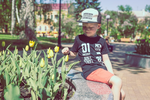 Young boy smells tulips flower in spring garden