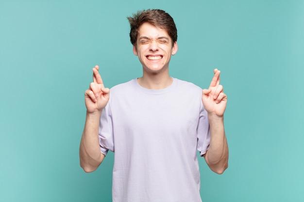 어린 소년은 웃고 걱정스럽게 두 손가락을 교차하며 걱정하고 행운을 빌거나 바라고 있습니다.
