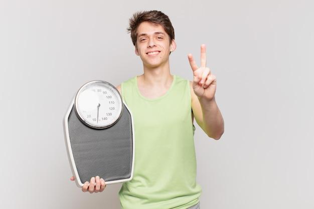 한 손 규모 개념으로 미소 짓고 행복하고 근심없고 긍정적인 표정으로 승리 또는 평화를 나타내는 어린 소년