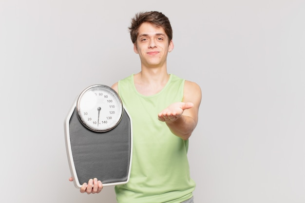 Young boy smiling happily with friendly, confident, positive look, offering and showing an object or concept scale concept