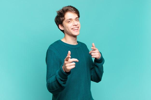 카메라를 가리키는 긍정적이고 성공적이며 행복한 태도로 웃고 있는 어린 소년, 손으로 총기 표시