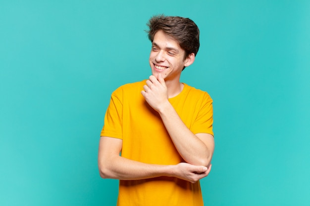 Young boy smiling with a happy, confident expression with hand on chin, wondering and looking to the side