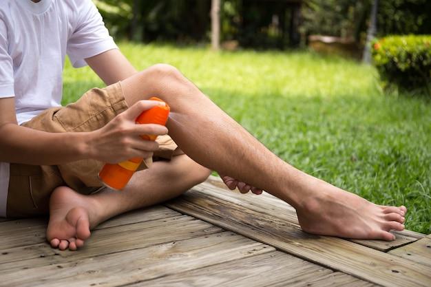 Мальчик распыляет репелленты насекомых на ногу с распылительной бутылкой