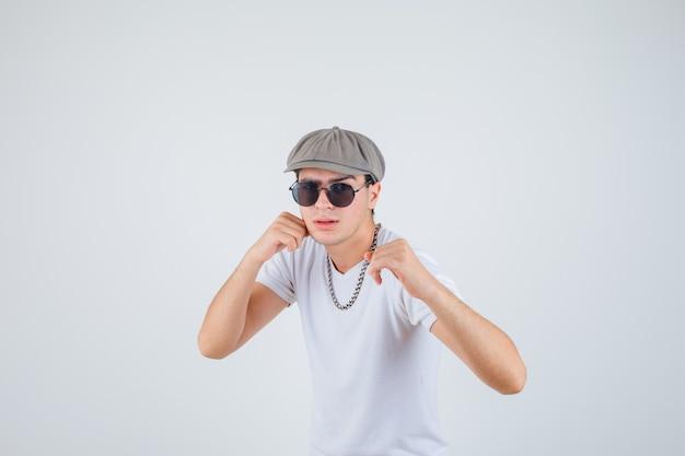 Giovane ragazzo in piedi in posa di lotta in t-shirt, cappello e guardando serio, vista frontale.