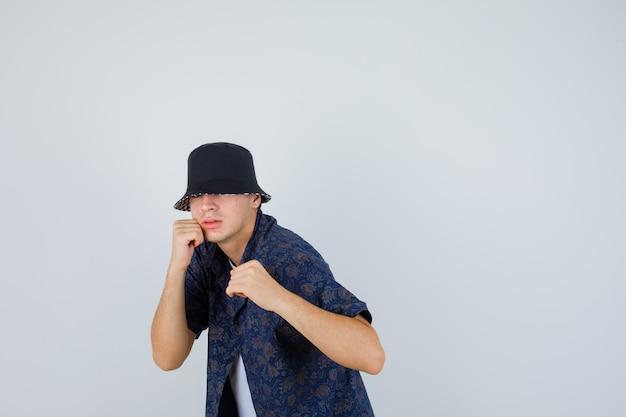 Giovane ragazzo che sta nella posa di lotta in maglietta bianca, camicia floreale, berretto e che sembra potente, vista frontale.