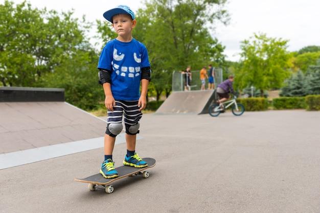 スケートパークでスケートボードに立っている少年が真剣な表情で遠くの何かを見ている