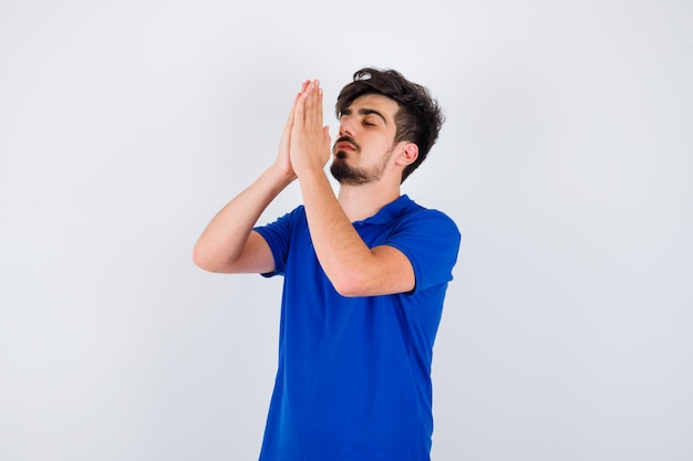 Giovane ragazzo in piedi in posa di preghiera in maglietta blu e sembra serio. vista frontale.