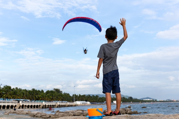 Young boy standing on the rock hands raised up looking at motor paraglider flying