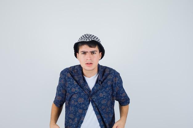 まっすぐ立って、白いtシャツ、花柄のシャツ、帽子に顔をゆがめ、真剣に見える少年。正面図。