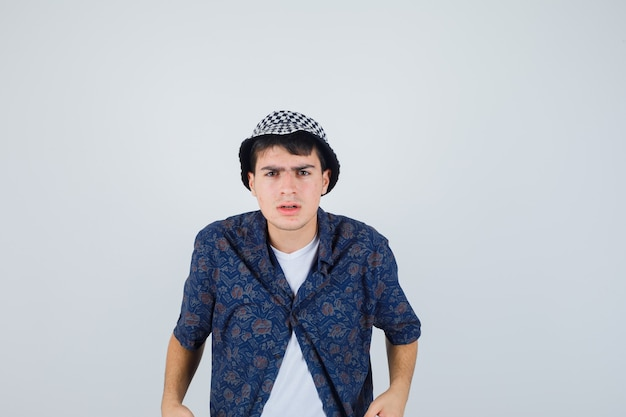 Young boy standing straight, grimacing in white t-shirt, floral shirt, cap and looking serious. front view.