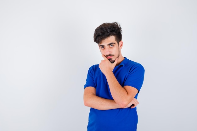 Giovane ragazzo in piedi in posa di pensiero in maglietta blu e guardando pensieroso. vista frontale.