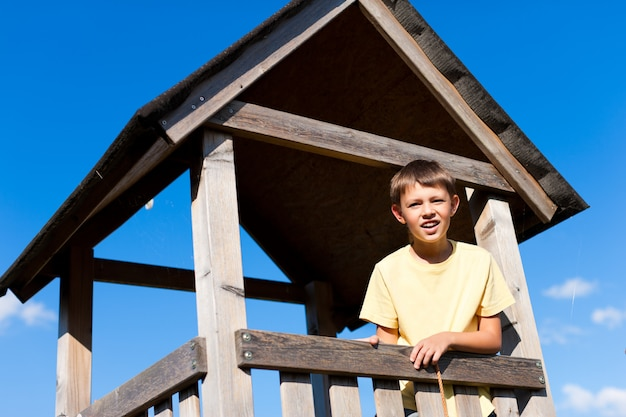 Young boy standing in wooden high seat