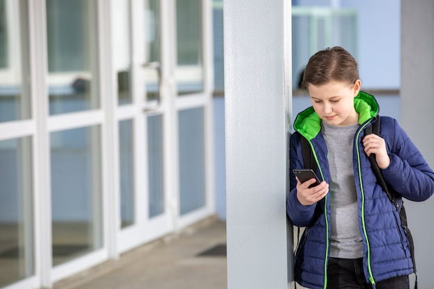 Young boy staying away from the school and playing games on the mobile, absence from school