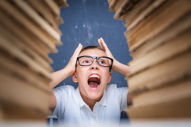 Young boy in stress getting crazy while studying and doing homework in children education concept sitting between two piles of books.
